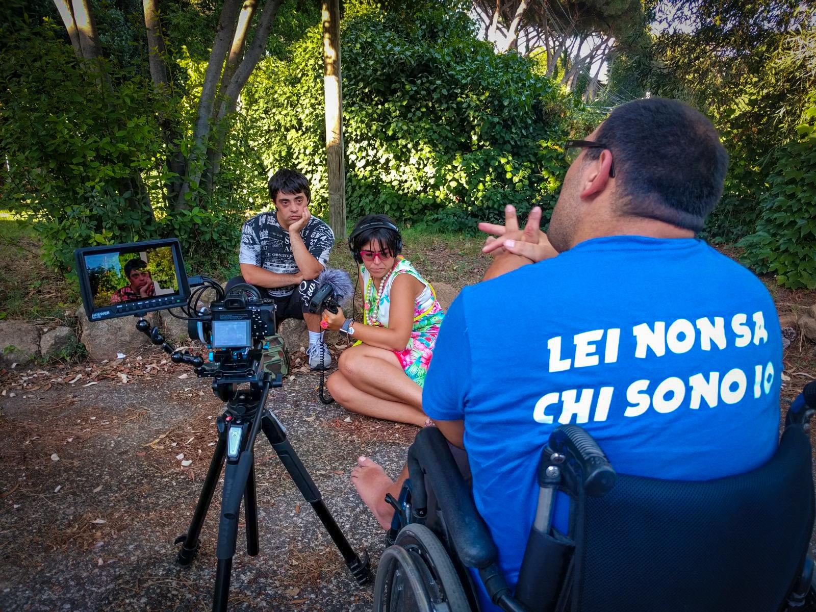 """sulla sedia del regista, Luca indossa una maglietta con la scritta """"Lei non sa chi sono io"""" mentre intervista Andrea"""