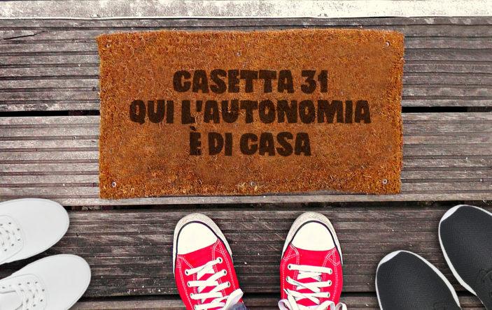 """Immagine raffigurante tre paia di scarpe vicino lo zerbino della casetta, con su scritto: """"Casetta 31. Qui l'autonomia è di casa""""."""